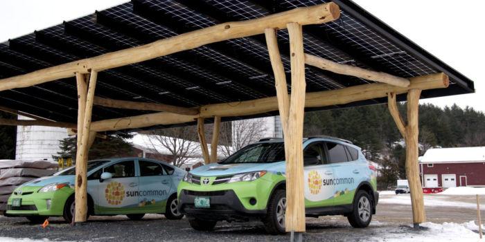 Деревянный автомобильный навес с одним пролетом. Балочная конструкция на две машины вмещает зарядное устройство и несколько рядов солнечных панелей. WholeTrees